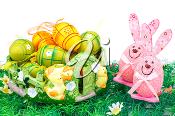 Easter decoration with colorful eggs in basket and bunnies on artificial grass.