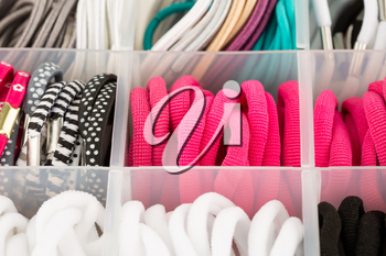 The assortment of colorful elastic hair bands in plastic box.