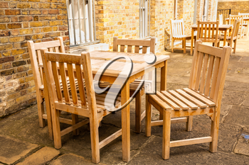 Wooden tables and chairs of outdoors cafe in London.