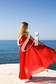 Pretty blond woman in the red dress at the beach in Cyprus.