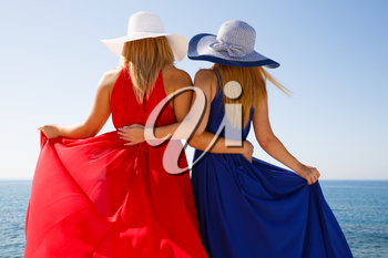 Blond women in the red and blue dresses at the beach in Cyprus.