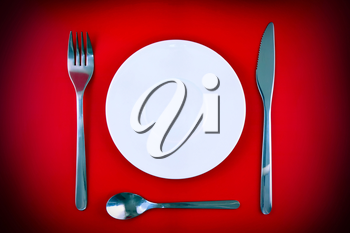 Table serving-knife,plate,fork on  red colour background.