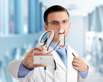 Friendly medical doctor with blank card (badge) in Hospital.