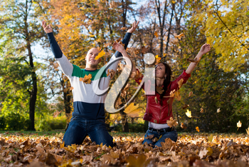 Young Couple Throwing Fall Leaves