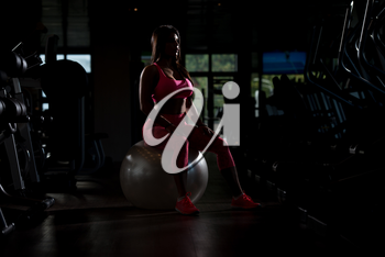 Young Mexican Woman Resting On Ball After Working Out In Fitness Cente