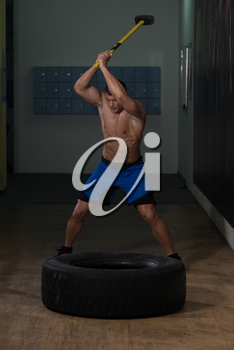 Athletic Man Hits Tire - Workout At Gym With Hammer And Tractor Tire
