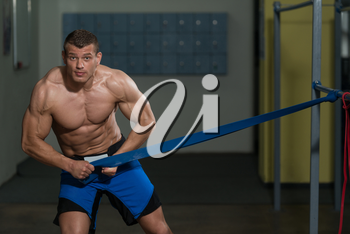 Muscular Man Training Stretching With Fitness Rubber Bands