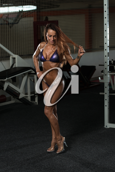 Young Woman Standing Strong In The Gym And Flexing Muscles - Muscular Athletic Bodybuilder Fitness Model Posing After Exercises