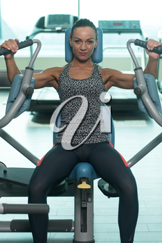 Portrait Of A Young Physically Fit Woman Exercising Chest On Machine - Muscular Athletic Bodybuilder Fitness Model Exercise In A Gym