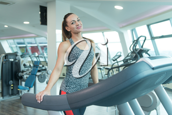 Young Woman Running On Treadmill In A Modern Fitness Center