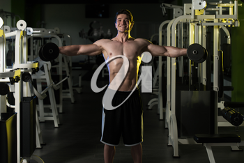 Young Man Exercising Shoulders With Dumbbells And Flexing Muscles - Muscular Athletic Bodybuilder Fitness Model Exercises