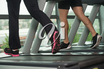 Close Up Of Couples Legs Running On Treadmill - Blurred Motion