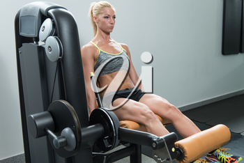 Leg Exercises - Young Woman Doing Leg With Machine In Gym