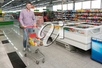 Handsome Young Man Shopping With Trolley For Fruits And Vegetables In Produce Department Of A Grocery Store - Supermarket - Shallow Deep Of Field