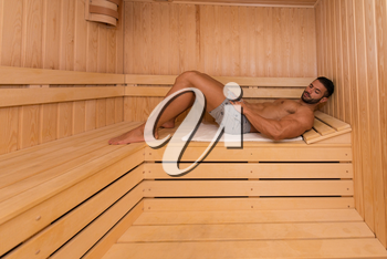 Happy Good Looking And Attractive Young Man With Muscular Body Relaxing In Hot Sauna