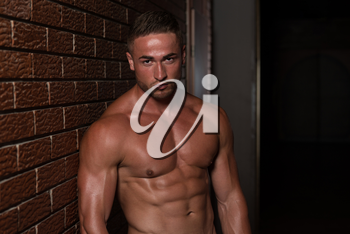 Healthy Young Man Standing Strong In The Gym And Flexing Muscles - Muscular Athletic Bodybuilder Fitness Model Posing After Exercises On Wall of Bricks