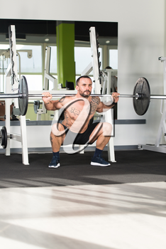Healthy Fitness Man Working Out Legs With Barbell In A Gym - Squat Exercise