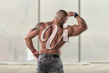 Handsome Young Man Standing Strong In Pants And Flexing Muscles - Muscular Athletic Bodybuilder Fitness Model Posing After Exercises