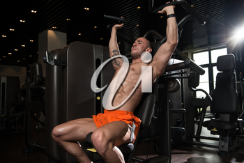 Handsome Muscular Fitness Bodybuilder Doing Heavy Weight Exercise For Shoulders On Machine With Cable In The Gym