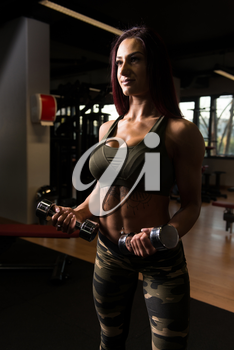 Young Woman Working Out Biceps In A Gym - Dumbbell Concentration Curls