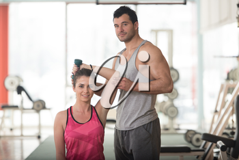 Personal Trainer Showing Young Woman How To Train Triceps Exercise With Dumbbell In A Gym