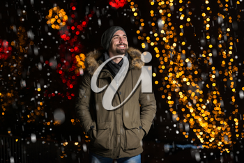 Having Fun at a Christmas Fairy - Young Cheerful Man Dressed Warm Is Standing In Holiday Market