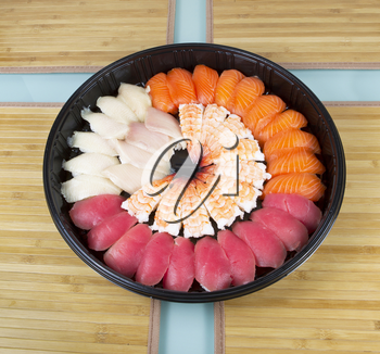 Assortment of fresh sushi placed neatly in a large plastic plate with bamboo place mats underneath on glass table