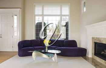 Large family living room with suede sofa, glass table in front of large double pane window with daylight coming in to room
