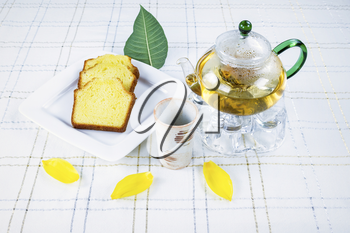 Horizontal photo of Green Tea pot (focus on cup and tea pot), Golden Lemon Pound Cake, yellow leafs and Tea cup on White Striped Table Cloth