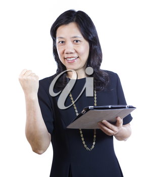A vertical portrait photo of a mature Asian woman wearing a dark dress while holding a folder and raising her fist in joy on white background