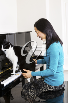 Vertical photo of mature woman laughing at family cat sitting on piano keyboard
