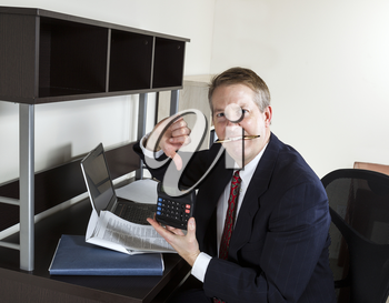 Mature man chewing pen while pointing thumbs down on calculator, with computer and papers on desk