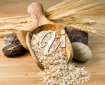Horizontal photo of rolled oats in wooden spoon with round stones and wheat stalks on natural bamboo wood