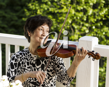 Horizontal photo of Senior Asian woman sitting down while playing the violin outdoors with green trees in background