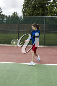 Young girl using a two handed backhand for lefthand tennis Player