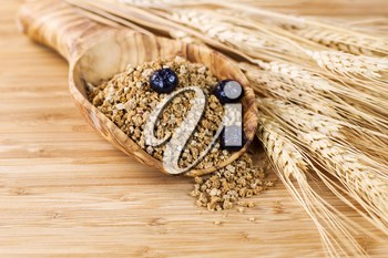 Closeup of horizontal photo of wooden spoon filled with Whole Grain Cereal with blueberries on top, wheat stalks on side with natural bamboo wood in background
