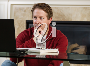 Photo of mature man, dressed casually while sitting down at glass table, working from home, looking at computer screen with fireplace in background