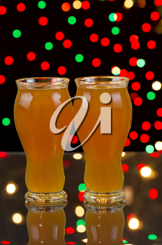 Vertical photo of two tall glasses, on glass table, filled with premium Amber Ale with party lights in background