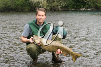 Horizontal photo mature man holding large king salmon while wading in river