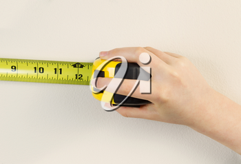 Horizontal photo of female hands using tape measure on interior home white wall