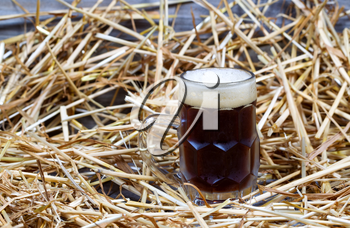 Horizontal image of a glass stein filled with dark draft stout beer on rustic wood and straw