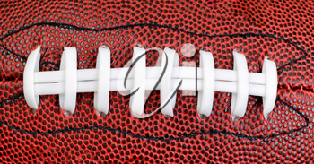 Close up of an American football in filled frame layout.