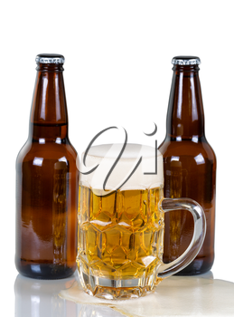 Golden colored beer flowing out of glass mug with two full bottles in background. Isolated on white with reflection.