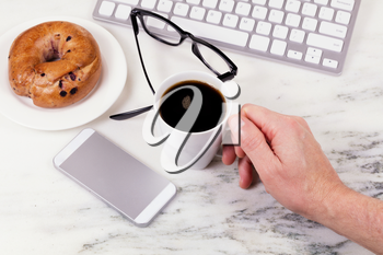 Overhead view marble counter top with male hand holding cup of coffee with computer keyboard, cell phone, reading glasses, and bagel on plate. Work at home concept.
