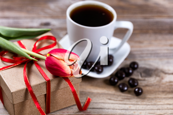 Single tulip resting on gift box with a cup of coffee and dark chocolate in background on rustic wood. Selective focus on front part of flower.