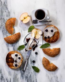 Overhead view of toasted bagels with cream cheese, sauce, blueberries, basil, sliced apple and coffee on white marble stone.