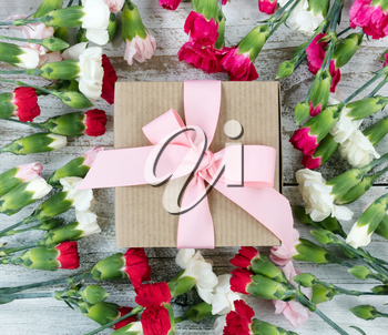 Colorful carnations surrounding gift box on white weathered wooden boards