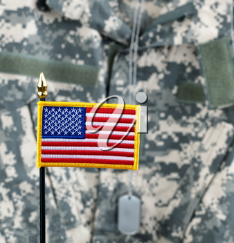 United States of America flag with camouflaged military uniform in background