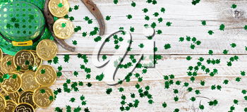 St Patrick day good luck hat, clovers and horseshoe with shiny gold coins forming left border on rustic white wooden boards