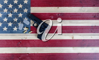 Military ID tags and weapon for Memorial, 4th of July and Veterans Day holiday on rustic US wooden flag